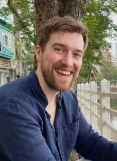 ein freundlich lachender Mensch in Nahaufnahme, an einem Flussufer in der Stadt sitzend. Karl Heuer